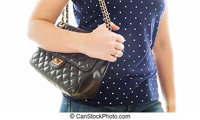 Closeup isolated photo of young woman holding hand on black leather handbag