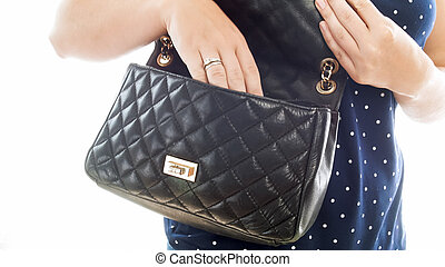 Closeup isolated photo of young woman searching with hand for something in handbag