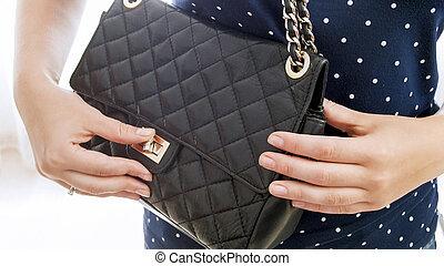 Closeup isolated photo of young woman unlocking her handbag