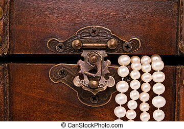 closeup jewellery box latch and pearls - closeup of wooden ...