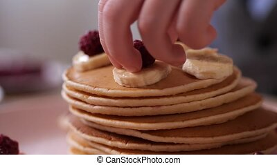 Closeup kid's hand putting raspberries on pancake
