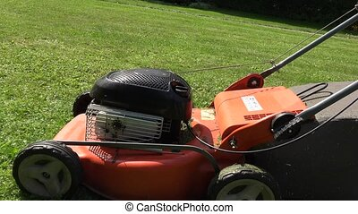 closeup lawn grass mower and gardener girl with bare legs...