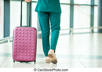 Closeup legs airplane passenger and pink baggage in an airport lounge going for flight aircraft. Young woman in international airport walking with her luggage