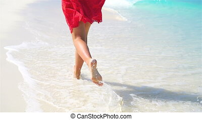 Closeup legs running along the white beach in shallow water. Concept of beach vacation and barefoot. SLOW MOTION.