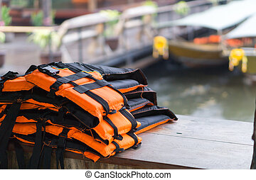 Closeup life jacket on wood table with river background, safety concept, selective focus