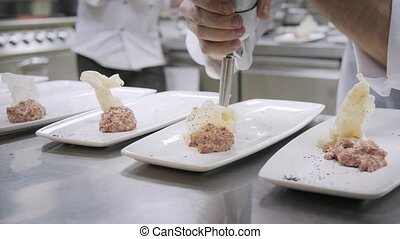 Closeup Line of plates dishes. Group chefs busy in...