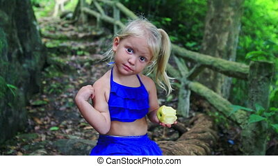 Closeup Little Blond Girl Eats Large Apple in Jungle