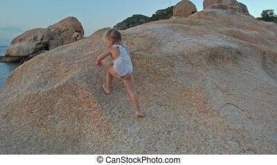 Closeup Little Girl Climbs up Large Bare Rock at Sunset on Beach