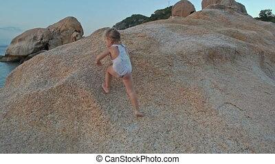 Closeup Little Girl Climbs up Large Bare Rock at Sunset on Beach