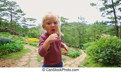 Closeup Little Girl Eats Shows Ice Cream on Path in Park