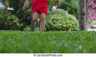 Closeup little girl playing outdoors runs on bright green beautiful grass with yellow flowers, outdoors at high angle feet of a small child who runs on the lawn near the house.