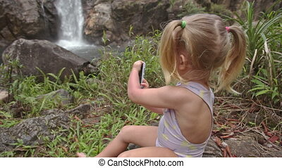 Closeup Little Girl Plays with Phone on Stone against Waterfall