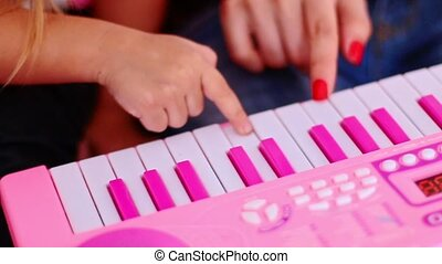 Closeup Little Girl Presses Keys on Pink Piano