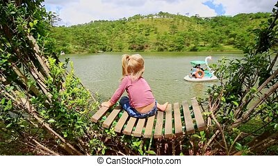Closeup Little Girl Sits on Bench In Clipped Bush Watches Lake