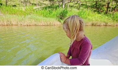 Closeup Little Girl Stands in Water Pedal Boat by Close Bank...