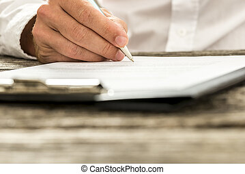 Closeup low angle view of male hand signing subscription form, legal document or business contract