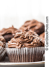 Closeup macro of chocolate cup cakes with ganache chocolate cream on the top