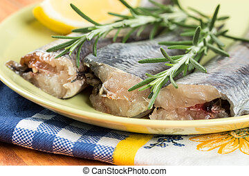 Closeup macro of fresh raw hake fish on the plate with rosemary
