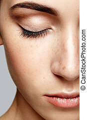 Closeup macro portrait of female face with closed eyes. Human woman half-face  with day beauty makeup. Girl with perfect skin and freckles
