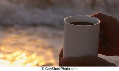 closeup male hand with mug of coffee against sea at sunrise