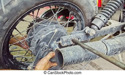 Closeup Man Assembles Wheel to Motorcycle in Repair-shop -...