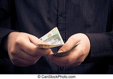 Closeup man calculating Polish money