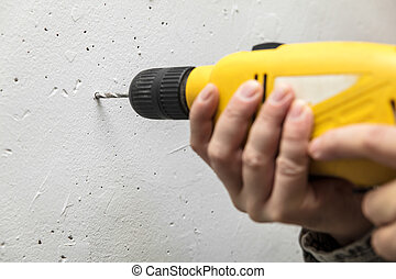 closeup, man drilled a hole in the wall