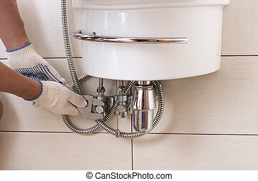 Closeup man fixing sink in a bathroom