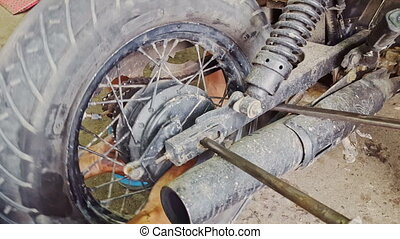 Closeup Man Hands Assemble Wheel to Motorcycle in...