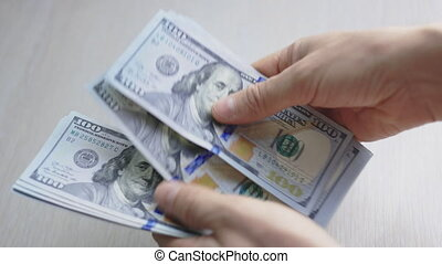 Closeup man hands counting one hundred dollar paper banknotes. Man counting 100 paper dollar bills