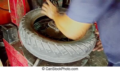 Closeup Man Hands Put Tire on Balance Machine in Repair-shop...