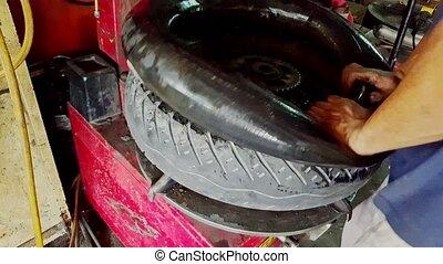 Closeup Man Puts Inner Tube into Tire on Balance Machine -...