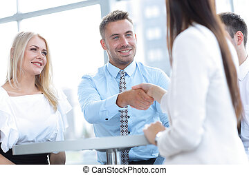 closeup. Manager shakes the hand of a woman client.