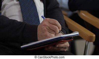 Closeup man's hands writing information at seminar - Closeup...