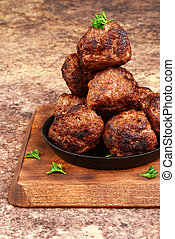 closeup meatballs in cast iron skillet on a wood cutting ...