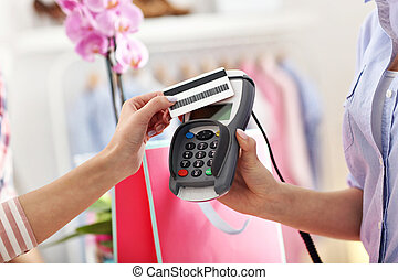 Closeup mid section of female customer paying in shop with...