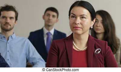 Closeup portrait of serious business woman in burgundy jacket listening speaker at marketing seminar. Middle aged member of training taking part in conference
