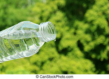 Closeup mineral water dropping from plastic bottle with green foliage in the backdrop
