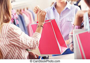 closeup, mittlerer abschnitt, von, weibliche , kunde, annahme, einkaufstüten, in, kleiderladen