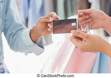closeup, mittlerer abschnitt, von, weibliche , kunde, annahme, einkaufstüten, und, kreditkarte, von, verkäuferin, in, kleiderladen