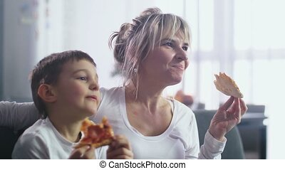 Closeup mom with son eating pizza and watching TV - Closeup...