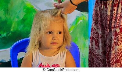 closeup mother braids little blonde girl's plait - closeup...