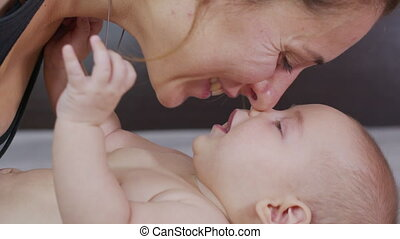 Closeup. Mother gently kissing baby enjoying loving mom playfully caring for toddler at home sharing connection with her newborn child. Healthy childcare
