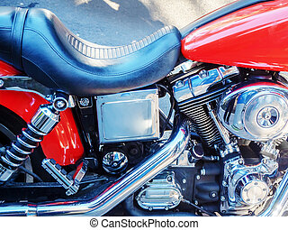 Closeup motorcycle engine side view reflective metal and black leather seat