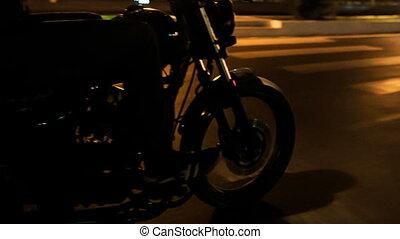 Closeup Motorcycle Speeds along Asphalt Road at Night