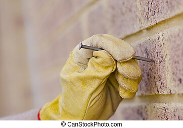 Closeup nail hand brick wall repair