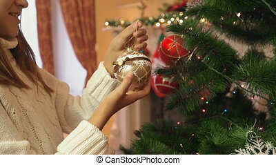 Closeup of 10 year old girl decorating Christmas tree with golden bauble
