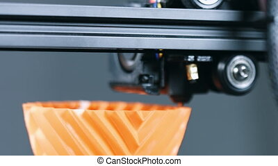 Closeup of 3D Printer printing a vase for home decoration with orange plastic Filament.