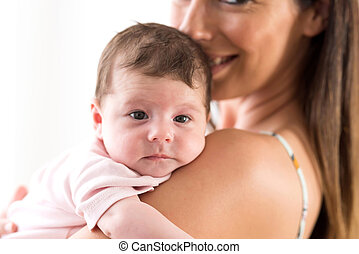 Closeup of a baby lying on her mothers chest