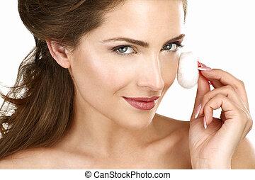 Closeup of a beautiful woman applying a beauty treatment